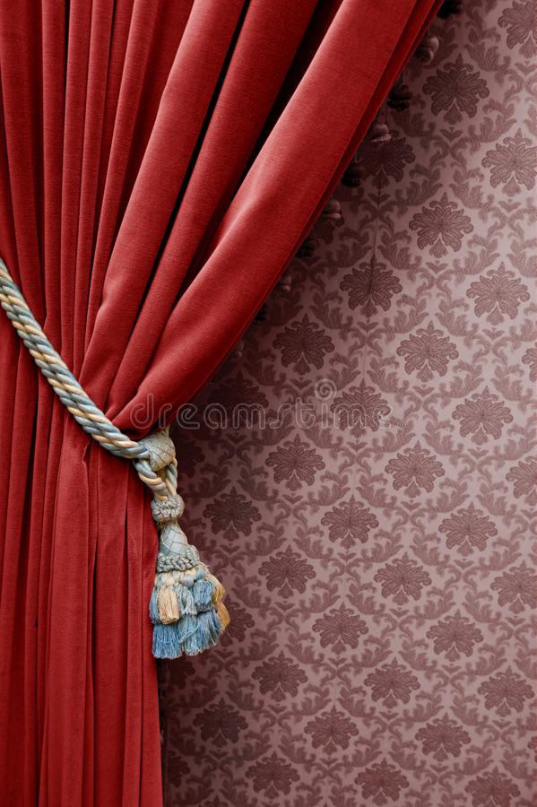 Vintage red curtain. On a floral wallpaper royalty free stock photo
