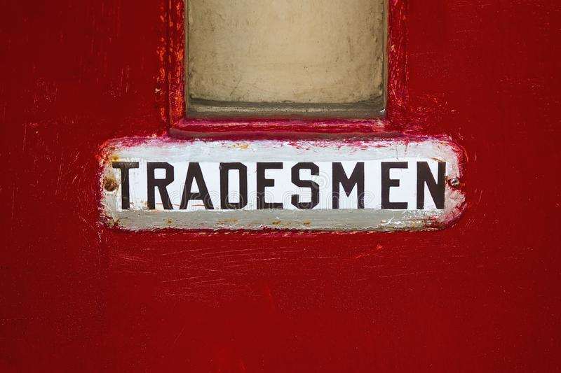 Red door, with tradesmen sign. Vintage red door, for entrance for trade royalty free stock photo