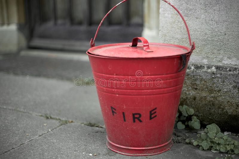 Vintage red fire bucket in the blurred background. Close up.  royalty free stock photo