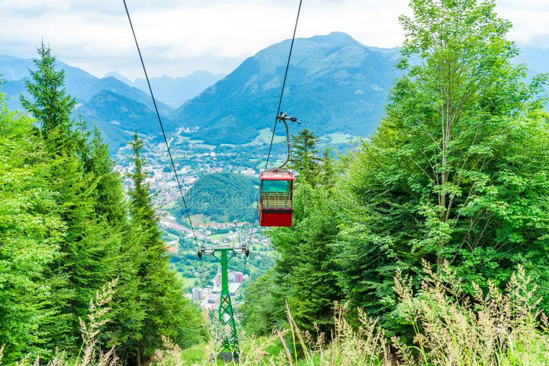 Vintage red gondola of Mount Katrin cable car, Austria. Colorful vintage gondola of Mount Katrin cable car and panoramic alpine view of peaks over Bad Ischl royalty free stock photography