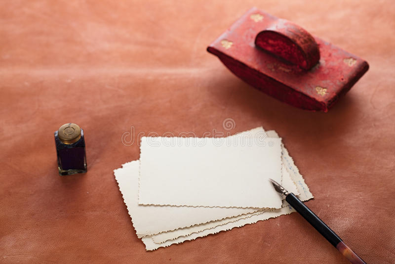 Vintage red leather ink blotter with retro post cards on leathe. R table, shallow dof royalty free stock photography