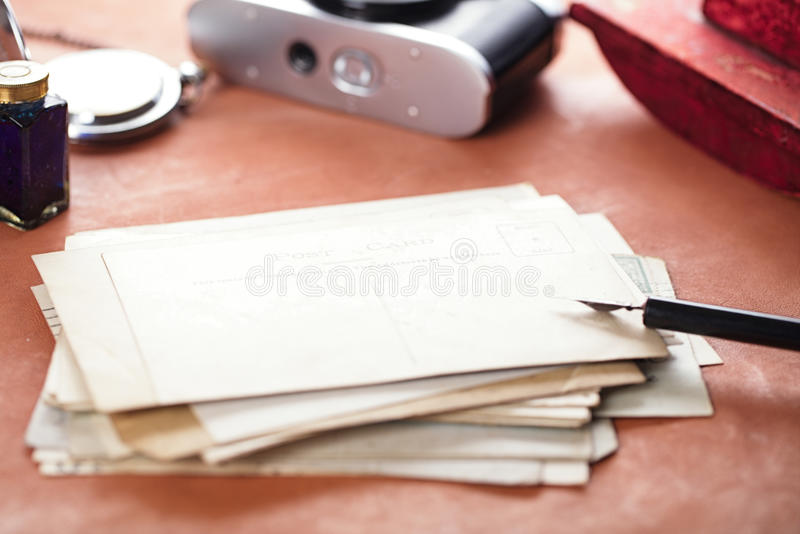 Vintage red leather ink blotter with retro post cards. On leather table, shallow dof stock photography