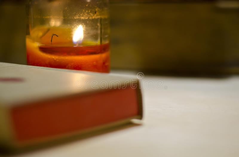 A vintage red paged book face down under candle light royalty free stock photos