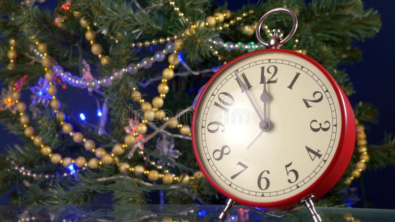 Vintage red retro alarm clock on the background of the Christmas tree, from five minutes to midnight, copy space for. Your text stock photos