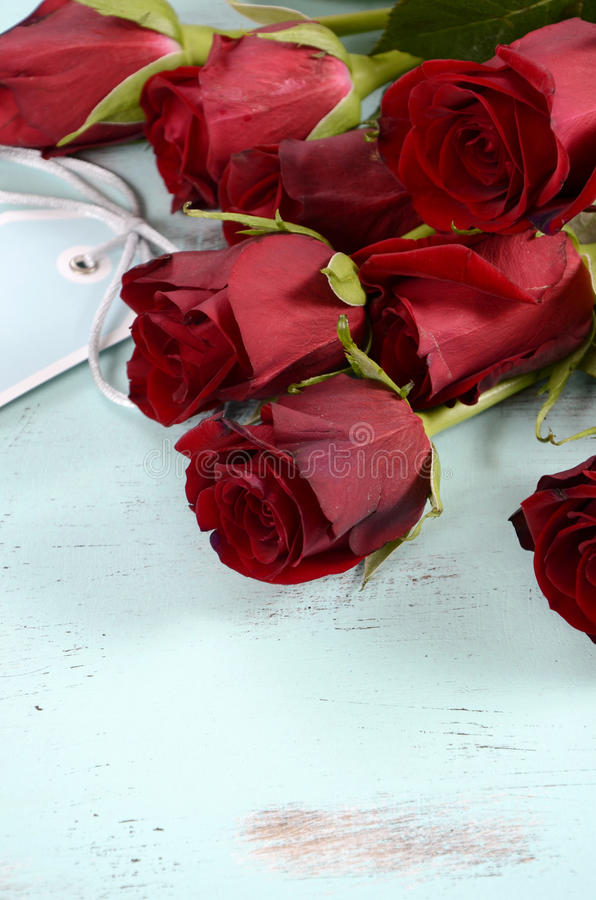 Vintage red roses gift. For Valentines Day, birthday or special occasion on pale aqua blue recycled distressed wood background stock photos
