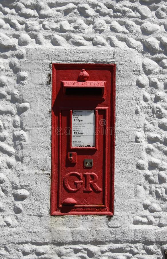 Vintage red UK postbox set in a white wall stock photography