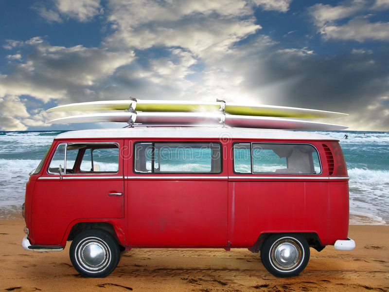 Vintage red van. A red volkswagen van or bus on the beach with two long surfboards on top. The beach is rough and two surf-boarders are out in the water. Sky can stock photography