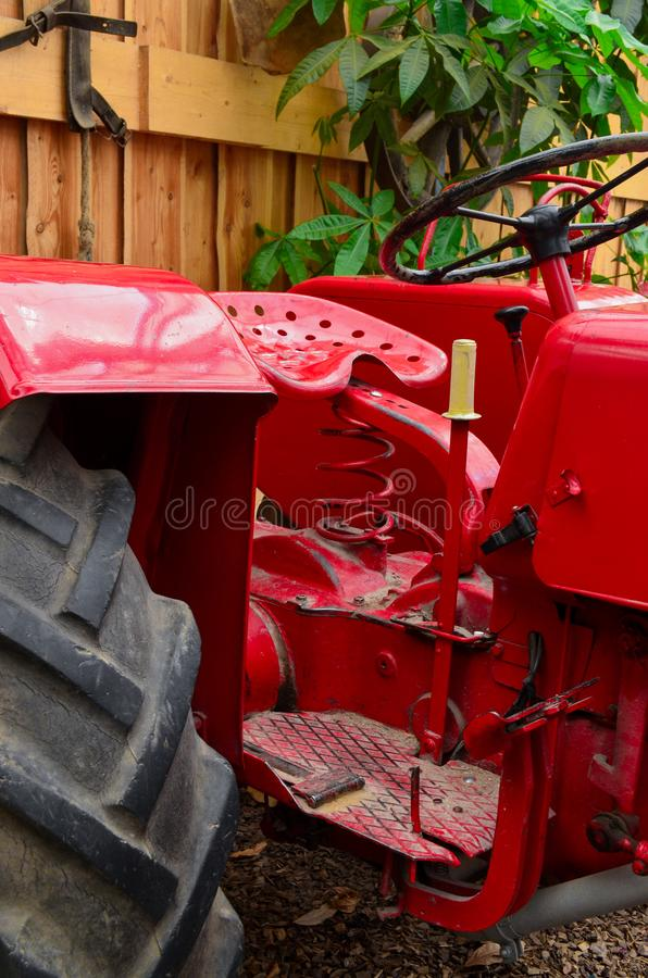 Vintage red vibrant tractor parked in a barn. With green leaves in the background stock photos