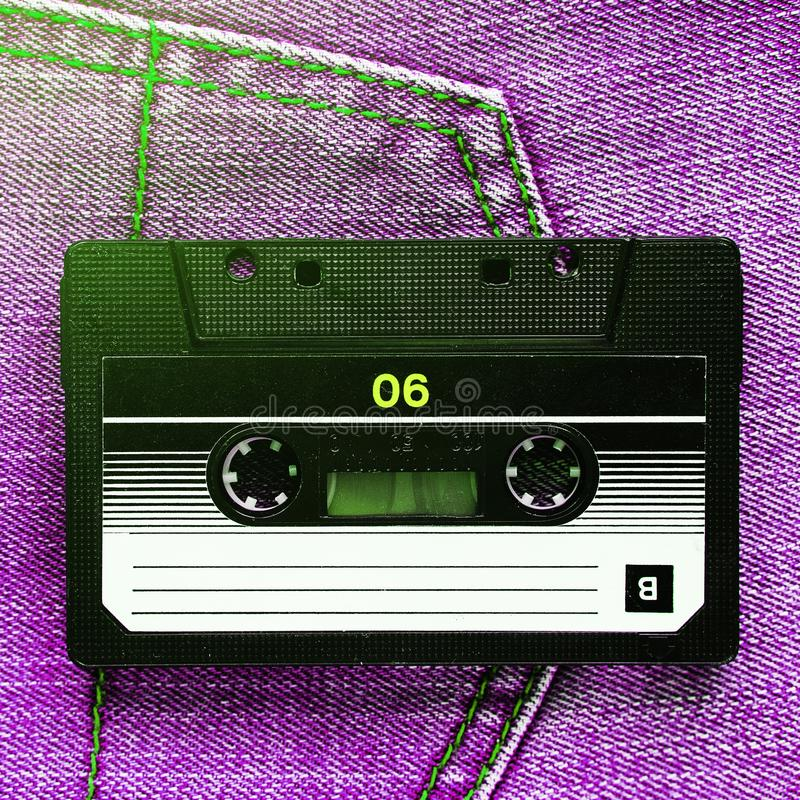 Vintage retro audio cassette on pink jeans background, close-up. Media technologies of the past 80-ies. Conceptual picture to royalty free stock image