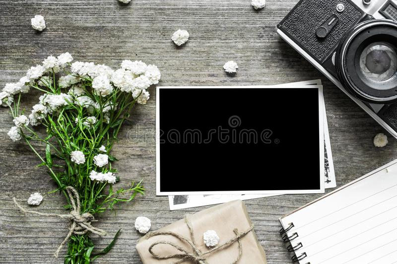 Vintage retro camera with blank photo frame and white flowers bouquet with lined notebook and gift box stock photos