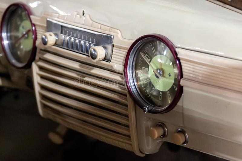 Vintage retro car dashboard with analog clock and audio radio system with buttons, handmade with wood and chrome for stock photography