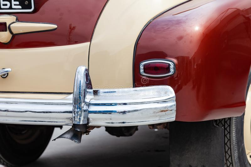 Vintage retro car rear chrome bumper with taillamp in beige and brown color, handmade with wood and chrome for restoration. Auto. Service industry stock image
