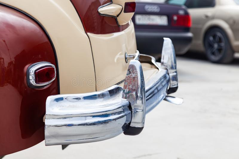 Vintage retro car rear chrome bumper with taillamp in beige and brown color, handmade with wood and chrome for restoration. Auto stock photography