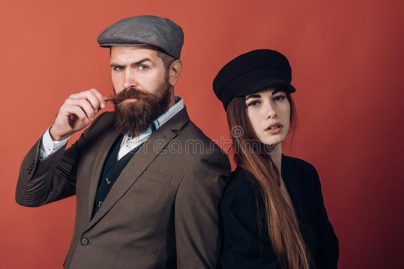 Vintage retro couple on red wall. Old style hat on bearded man and black fashion cap on beauty woman. stock images