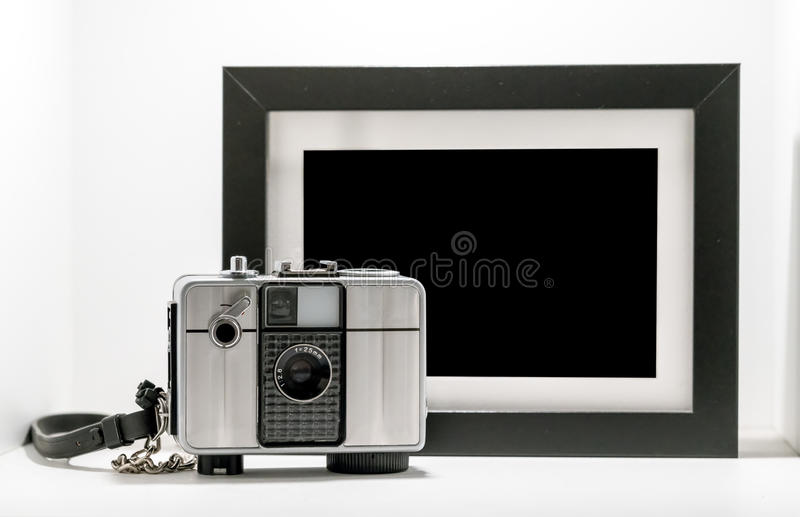 Vintage retro film camera with black and white picture frame iso. Vintage retro film camera with black and white picture frame on white background stock image