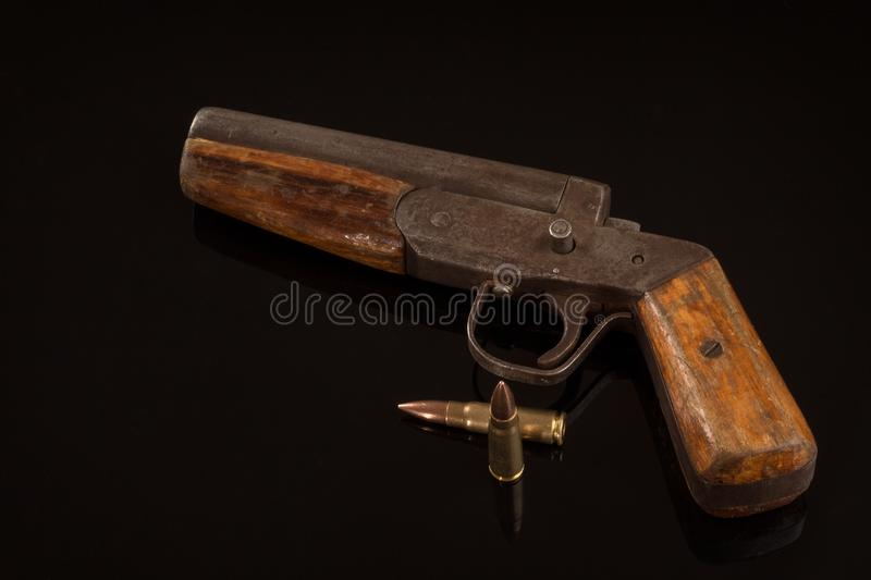 Vintage retro handgun pistol and two bullets isolated on black background stock photography