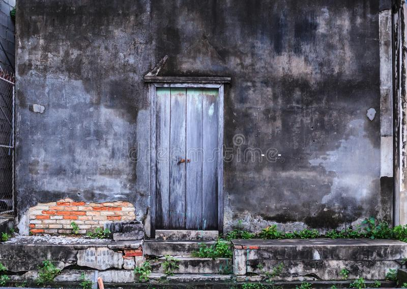 Vintage retro Home interior architectural design, plain old aged tropical weathered textured faded color wood panel board door and. Moldy wall of traditional royalty free stock image