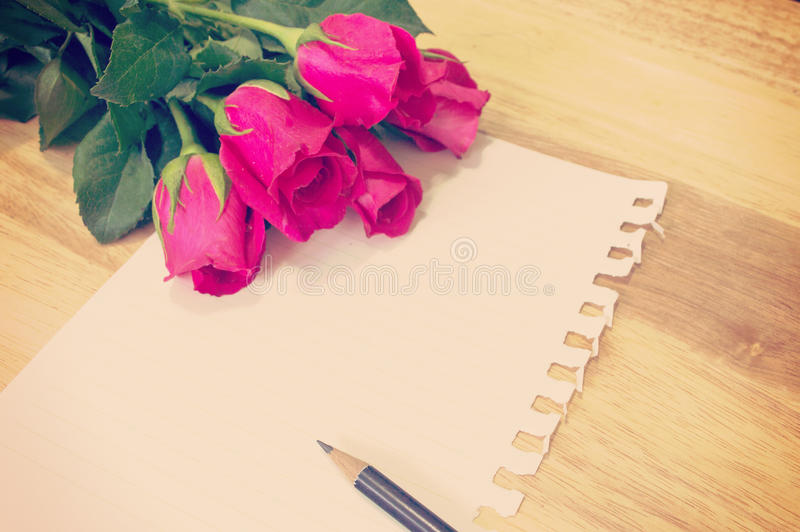 Vintage,retro of note book paper and pencil with roses royalty free stock photo