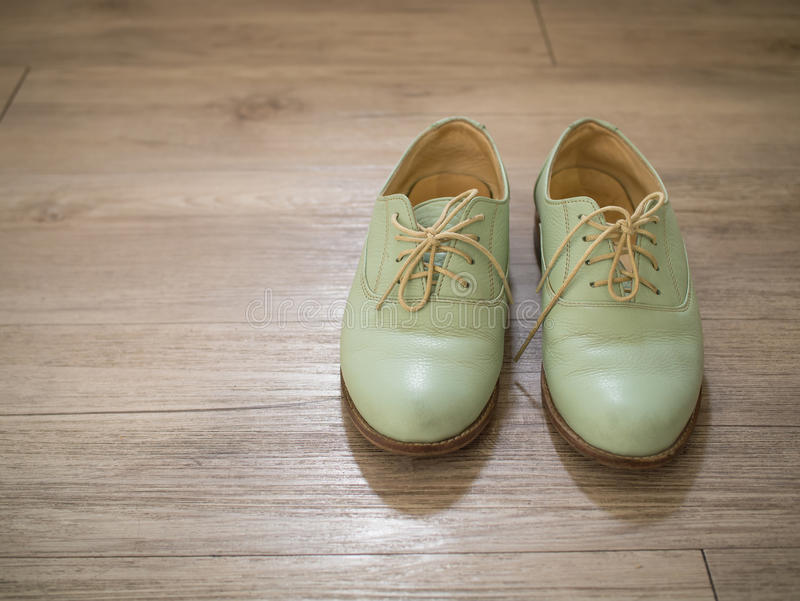 Vintage retro a pair of women green leather shoes on a wooden floor royalty free stock photos