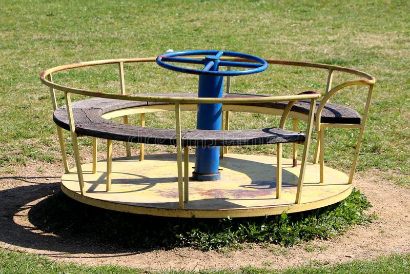 Vintage retro partially rusted outdoor public playground equipment made of metal with faded colors and wood in shape of roundabout royalty free stock image