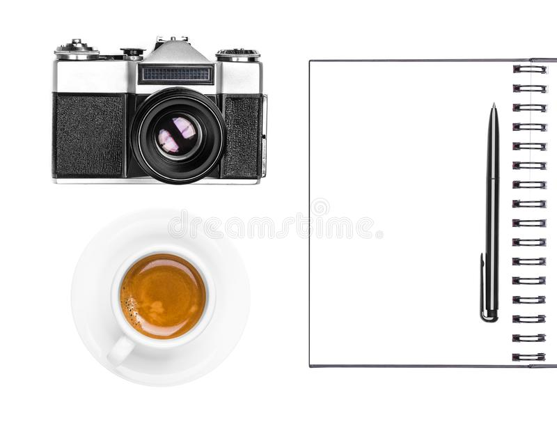 Vintage retro photo camera, coffee cup, notepad and pen isolated on white background. Flat lay. Top view stock images
