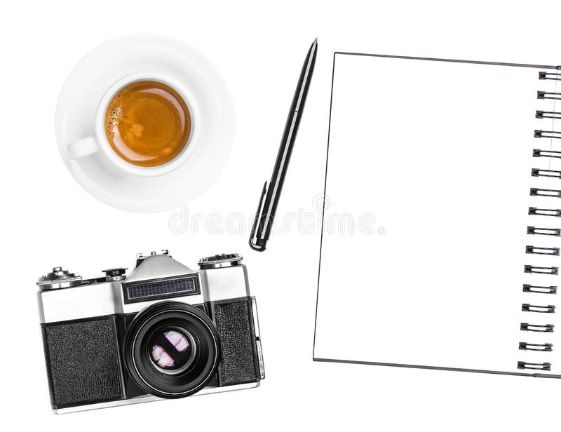 Vintage retro photo camera, coffee cup, notepad and pen isolated on white background. Flat lay. Vintage retro photo camera, coffee cup, notepad and pen isolated stock photography