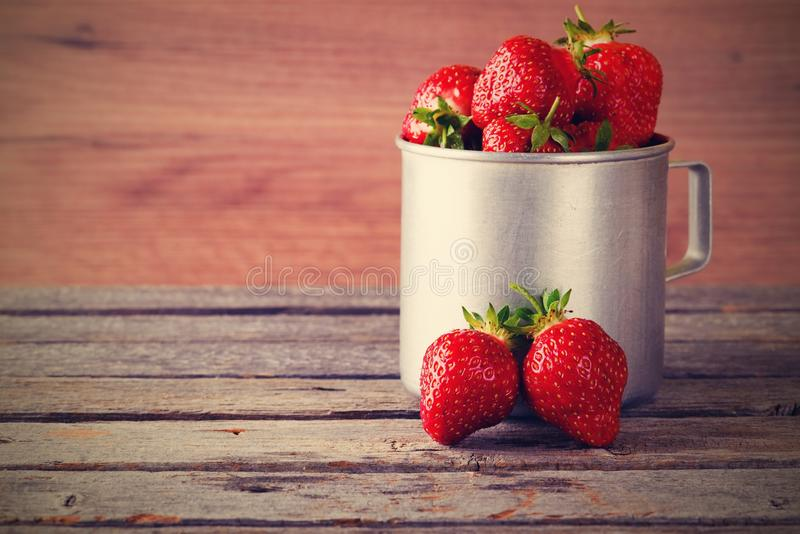 Vintage retro photo of two strawberries in front of aluminum cup stock images