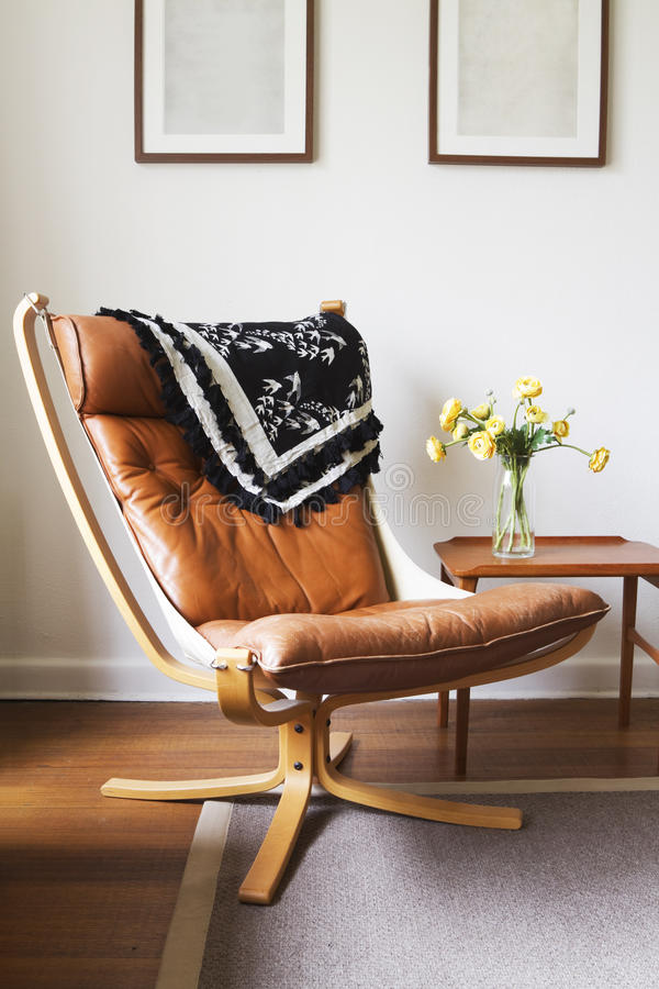 Vintage retro tan leather danish chair and table. With vase of flowers royalty free stock image