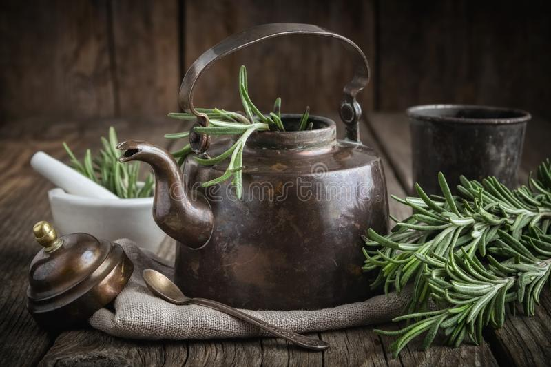 Vintage retro teapot, bunch of fresh rosemary herbs, cup of healthy herbal tea and mortar. royalty free stock image