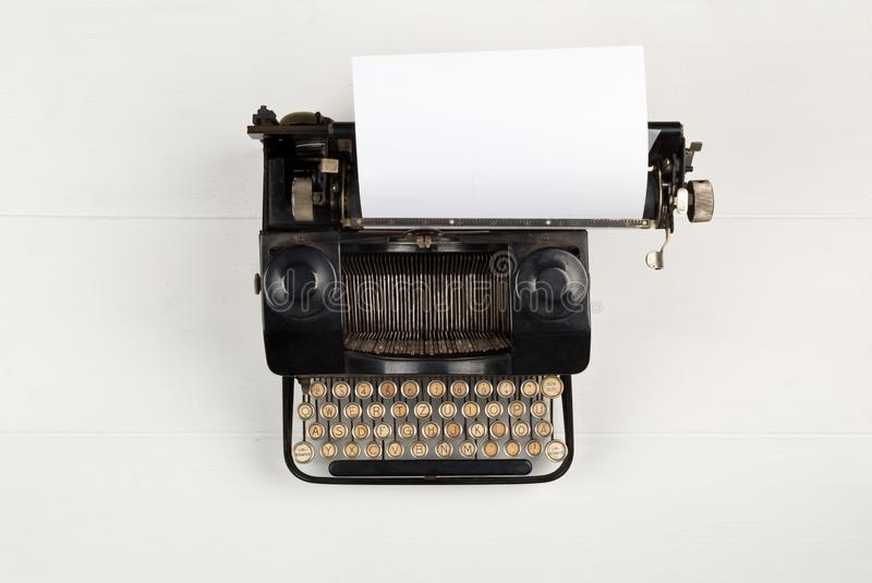 Vintage retro typewriter with sheet of paper on white table background top view flat lay from above with copy space - journalism. Vintage retro typewriter with royalty free stock photos