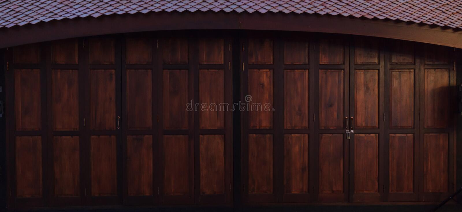 Vintage retro wooden door store front. Home interior architectural design, plain tropical dark brown textured wood panel board. Wall in old traditional boutique stock photo