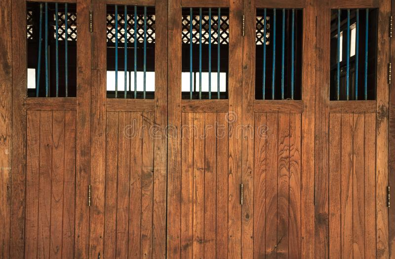 Vintage retro wooden doors and window panes with bars, home interior architectural design against plain tropical dark brown. Textured wood panel board wall in stock photo