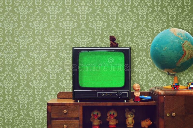 Vintage room with wallpaper, old fashioned shelf, retro tv, globe, rubber toys royalty free stock photos