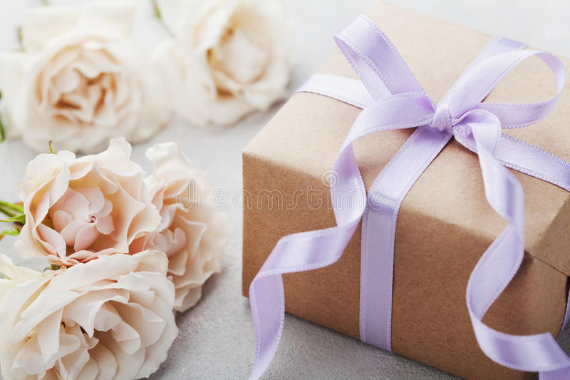 Vintage rose flowers and gift box with ribbon on light table. Greeting card for Birthday, Womens or Mothers Day. Vintage rose flowers and gift box on light royalty free stock photography