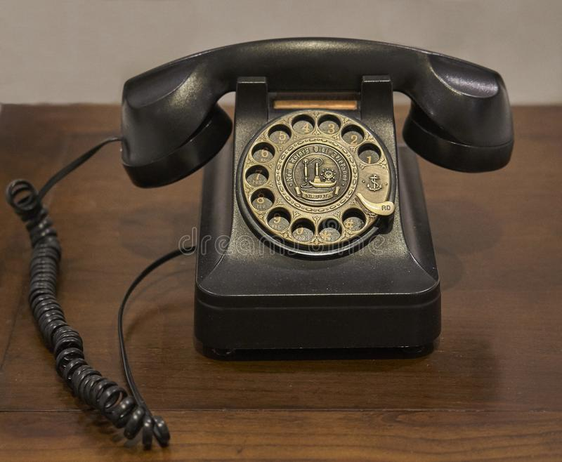A vintage rotary dial telephone on an old wooden table. A vintage dark brown rotary dial telephone placed on an old wooden table royalty free stock image