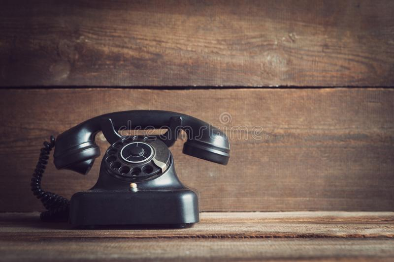 Rotary dial telephone. Vintage rotary dial telephone on wooden board with copy space royalty free stock image