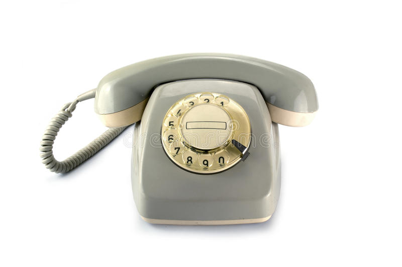 Vintage rotary phone, gray yellowed plastic on a white backgrou royalty free stock photos
