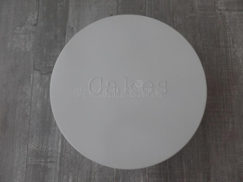 Vintage round cake tin with embossed writing on the front royalty free stock photography