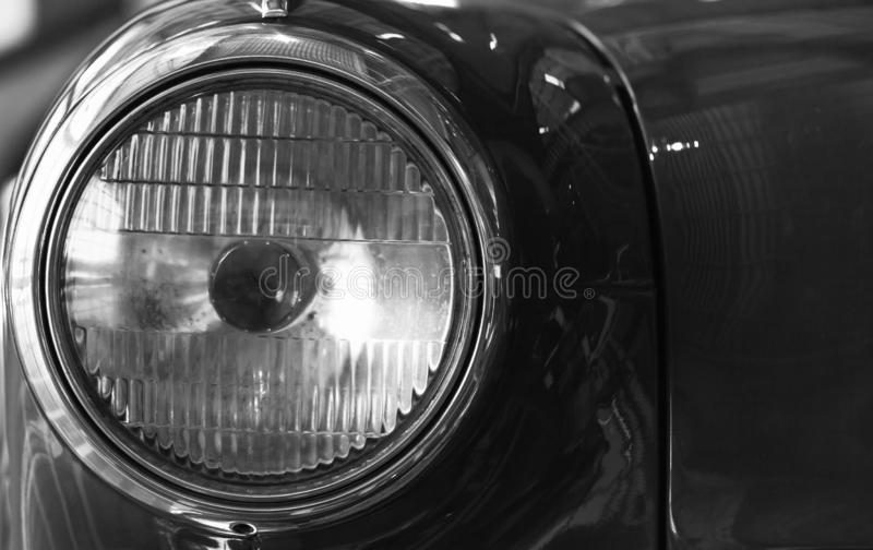 Vintage round car headlight. Old timer details. Close up black and white photo with soft selective focus stock image