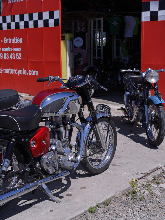 Vintage Royal Enfield motorcycle and other British motorcycle outside a French garage. Vintage Royal Enfield motorcycle and other motorcycle outside a French royalty free stock images