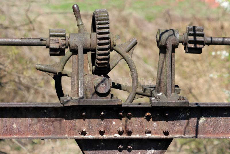 Vintage rusted abandoned dam cogwheel gears and metal poles mounted on heavy beam and connected with multiple screws stock photos