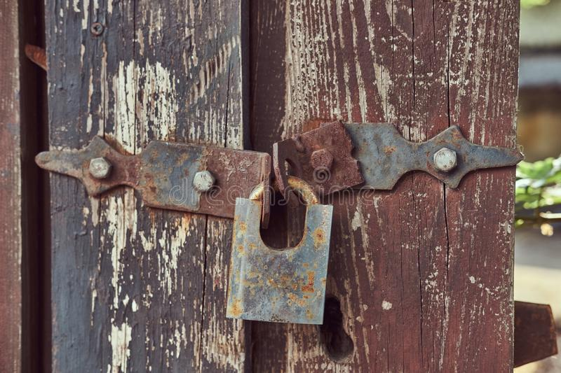 Close-up image of a vintage rusted lock on an old worn wooden fence. royalty free stock photos