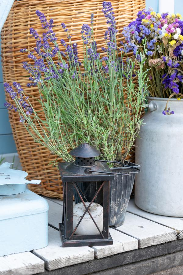 Vintage rustic candle lantern with lavander and dried flowers standing outsite on wooden porch royalty free stock photography