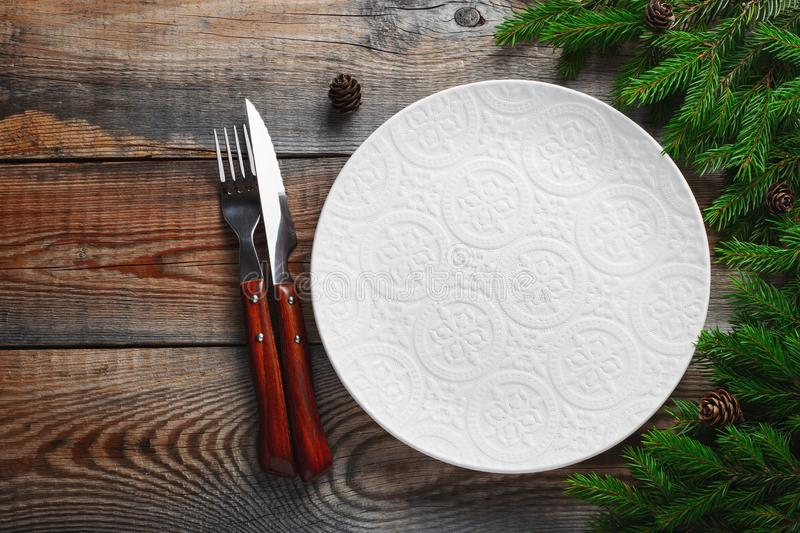 Vintage or rustic christmas table setting from above. Elegant empty white plate, cutlery and natural pine tree branch on royalty free stock photos