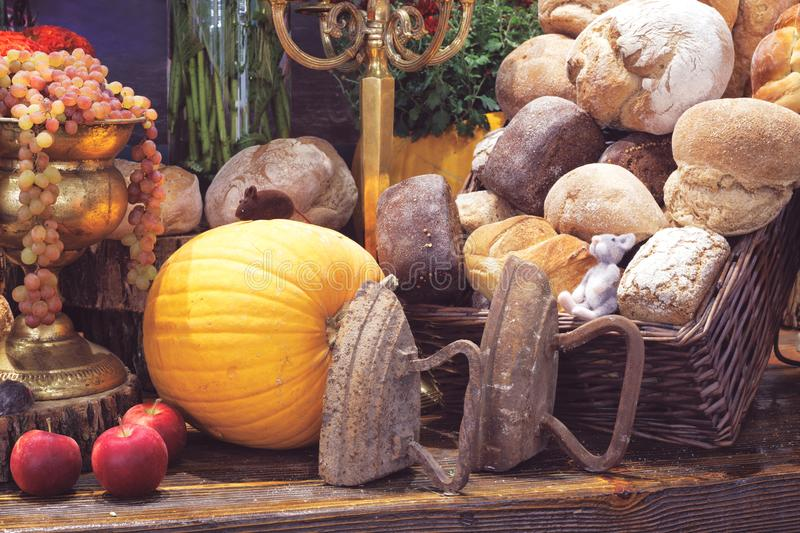 Vintage rustic still life with irons, pumpkins, fruits, bread and toy mice. rustic concept royalty free stock photography