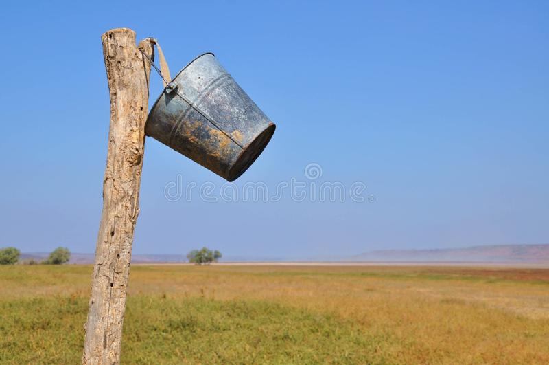 Vintage rusty galvanized bucket is hanging on rough wooden pole. On clear light blue sky background. Rustic landscape near Kuyalnik liman salt lake in Odessa royalty free stock photo