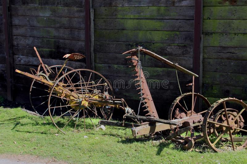 Vintage rusty old farm equipment lying unused on a grass verge. In a farmyard stock photos