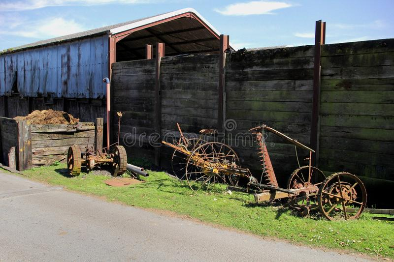 Vintage rusty old farm equipment lying unused on a grass verge i. N a farmyard, against a large wooden fence with corrugated iron barn on a sunny summer day stock photos
