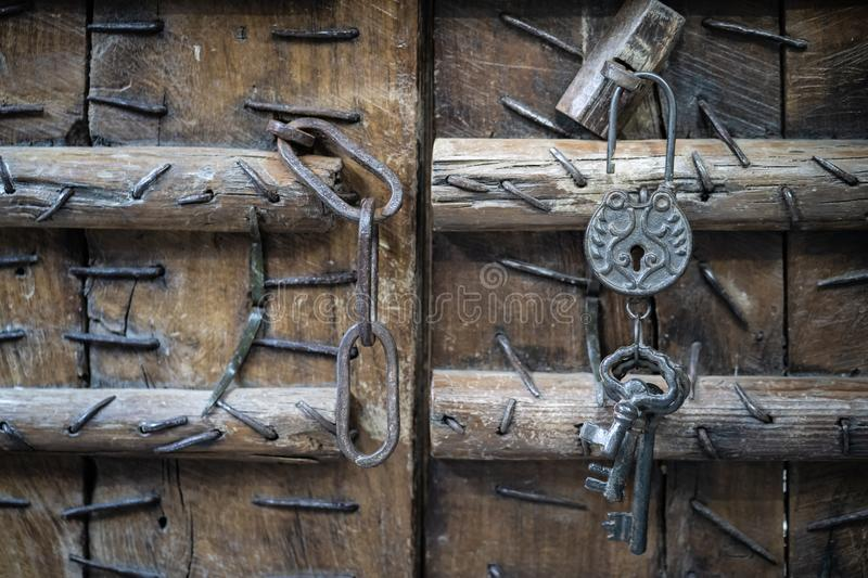 Vintage rusty padlock and old keys with old wooden door backgro royalty free stock images