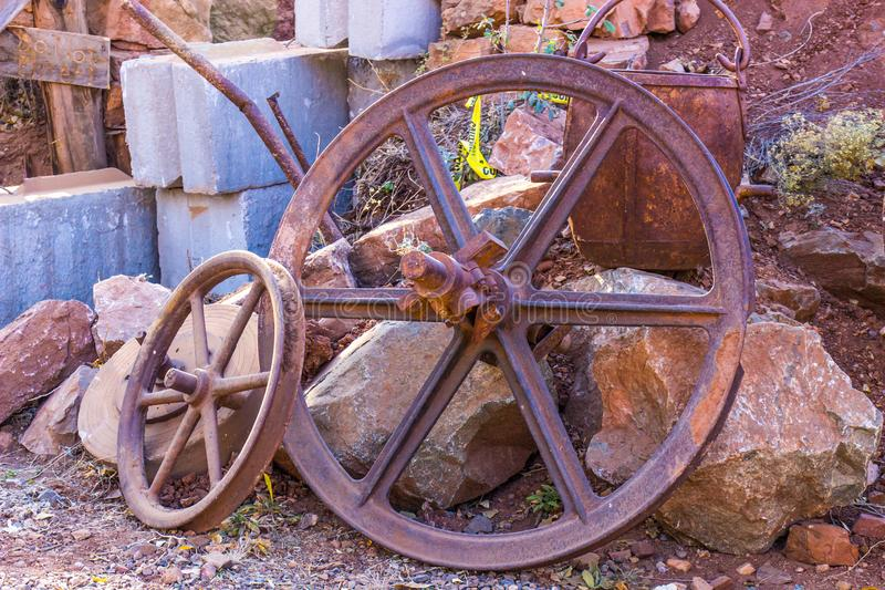 Vintage Rusty Pitted Wheels And Ore Bucket. Vintage Rusty Pitted Iron Wheels With Spokes And Ore Bucket With Handle royalty free stock images